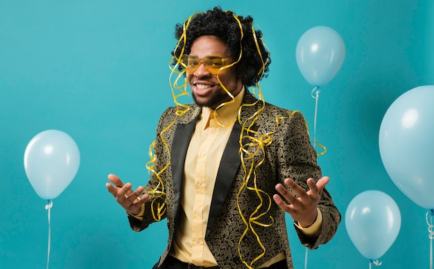 Man in suit and sunglasses at party with balloons