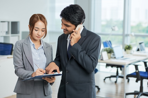 Man in suit talking on phone and woman making notes
