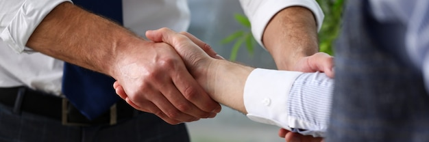 Man in suit and tie give hand as hello in office closeup