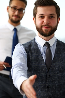 Man in suit and tie gives hand as hello in office