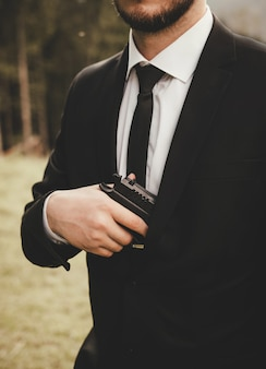 A man in a suit with a beard, jacket and white shirt, black tie, holding a gun in his hand jn the street.