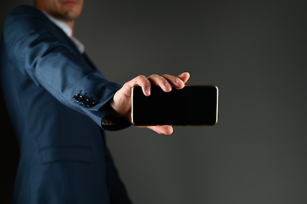 A man in a suit with outstretched hand holds a phone