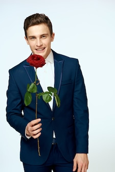 A man in a suit with a rose in his hands a gift date light wall.