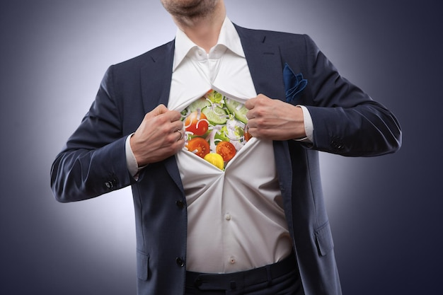 Man in suit with salad inside isolated on dark