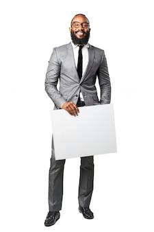 L'uomo in tuta con un poster bianco