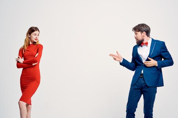 A man in a suit next to a woman in a red dress communication fashion isolated background