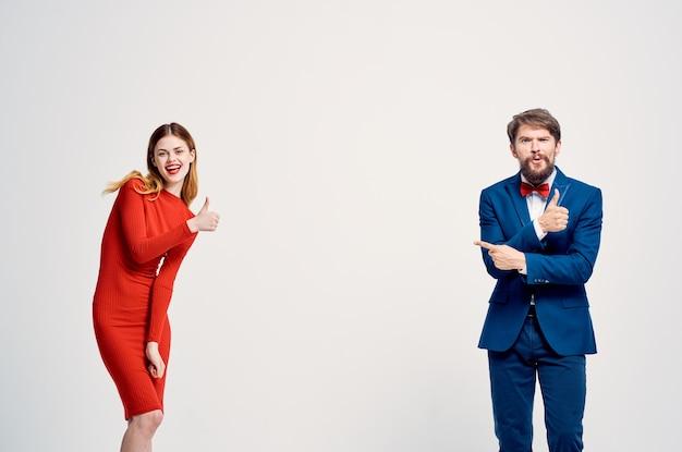 A man in a suit next to a woman in a red dress communication fashion light background