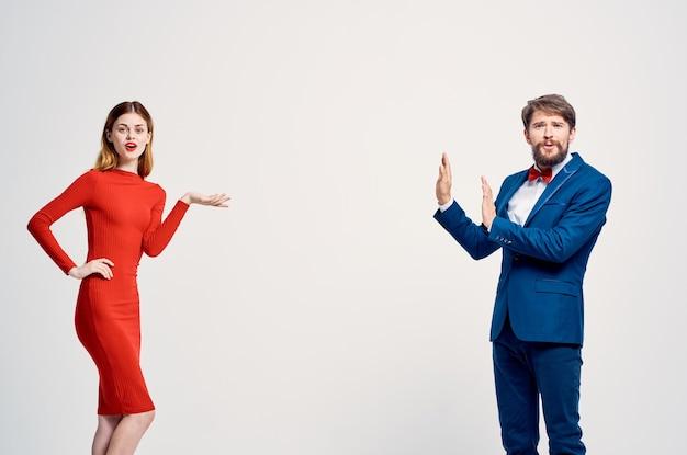 A man in a suit next to a woman in a red dress communication fashion studio
