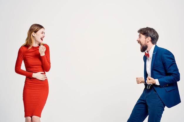 A man in a suit next to a woman in a red dress emotions hand gestures light background