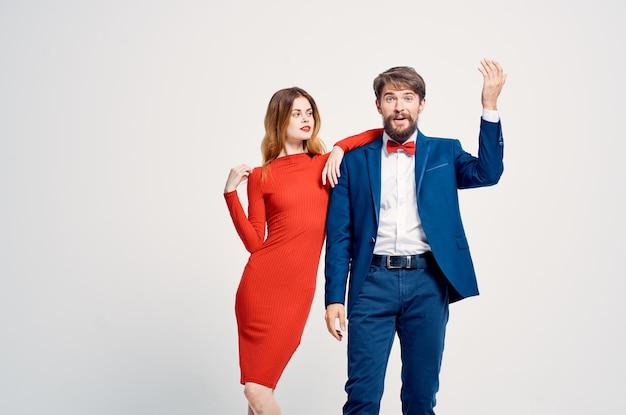 A man in a suit next to a woman in a red dress romance happy light background