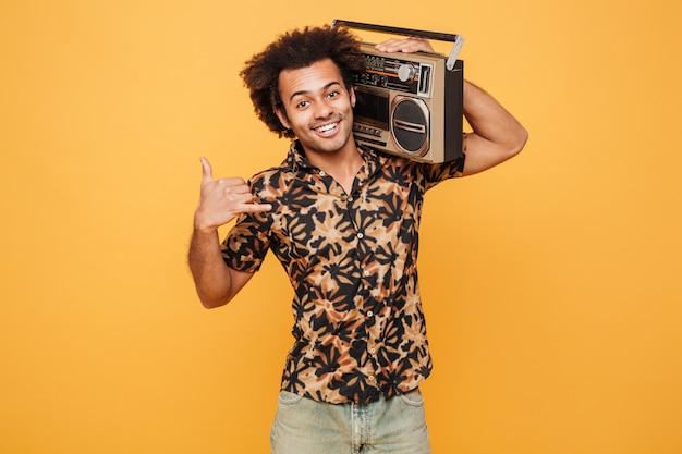 Man in summer clothes holding boombox on his shoulder