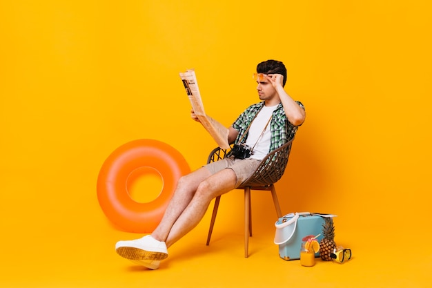 Man in summer outfit removes glasses and reads newspaper. portrait of guy on orange space with suitcase and rubber ring.