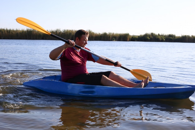 A man in summer swims on the river in a kayak