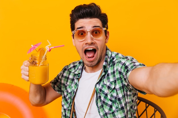 Man in sunglasses and green shirt takes a selfie and looks at the camera with surprise. portrait of guy with glass of cocktail on isolated space.