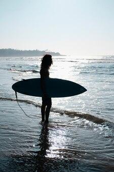 모래 해변에서 서핑 보드에 앉아 남자 서퍼