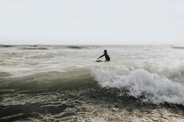 Человек, занимающийся серфингом на пляже