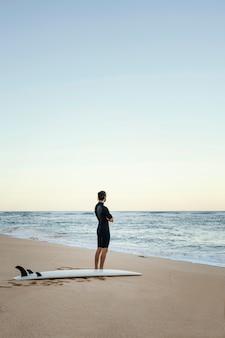 Uomo e tavola da surf al colpo lungo dell'oceano