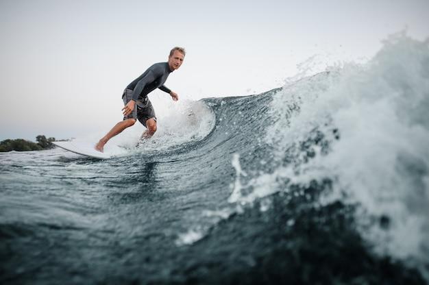青い水の下でボードをサーフィンする男