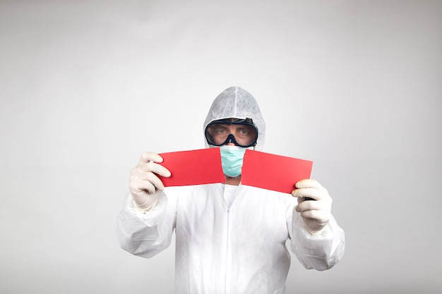 Man in surgical mask with white protective suit and a red halved poster isolated in studio on white background. prevention against coronavirus.