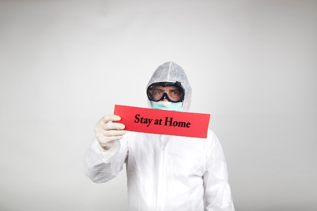 Man in surgical mask with white protective suit and a red sign with the word stay home isolated in studio on white background. new coronavirus