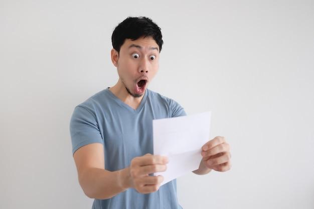 Человек удивлен и шокирован письмом в руке на изолированной стене.