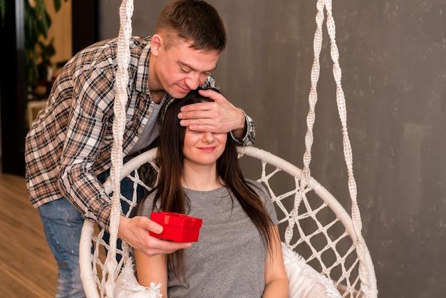 Man surprising girlfriend on hammock chair with present