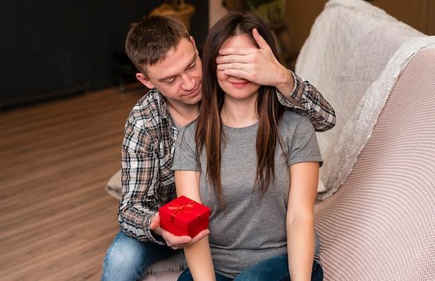 Man surprising girlfriend with present
