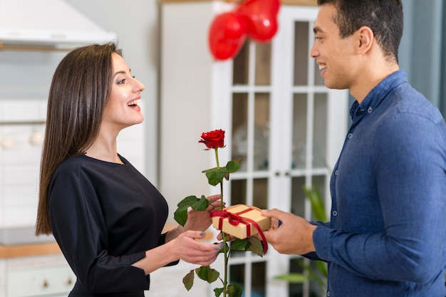 Man surprising his girlfriend with a valentine's day gift