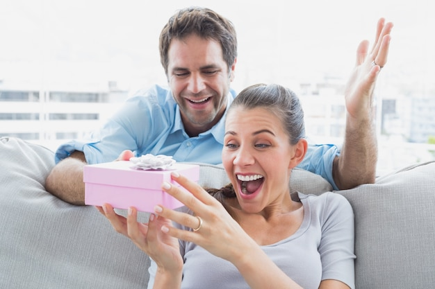 Man surprising his pretty girlfriend with a pink gift on the sofa