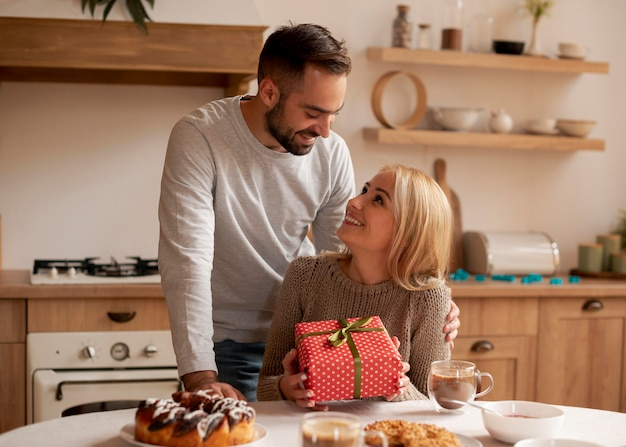 Man surprising woman with present