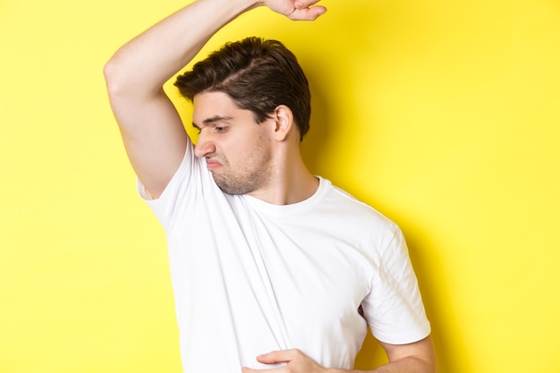 Man in sweat smelling his armpit standing in white tshirt and grimacing from stinky clothes