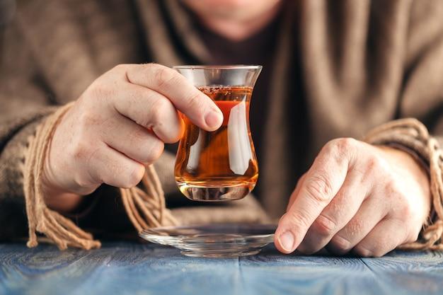 Man in sweater drink hot tea