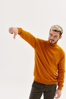 Man in sweater showing thumb down displeased emotion light background