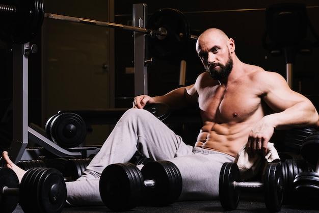 Man in sweatpants amidst barbells