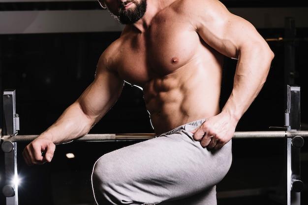 Man in sweatpants posing near barbell