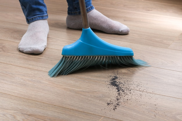 The man sweeps the debris into a blue scoop with brush.