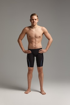A man swimmer in goggles for swimming in full growth on a gray background, preparing an athlete for a swim, copy space