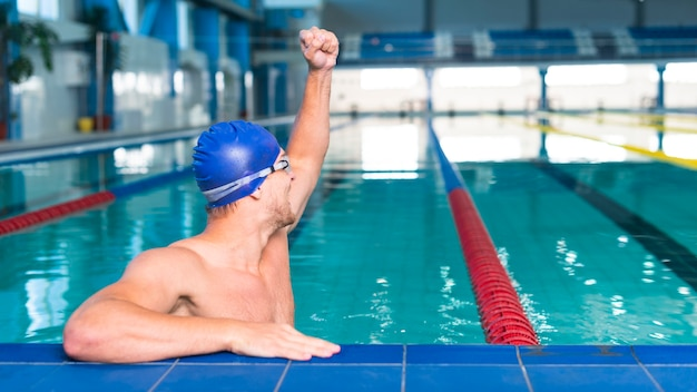 Man swimmer raising his hand