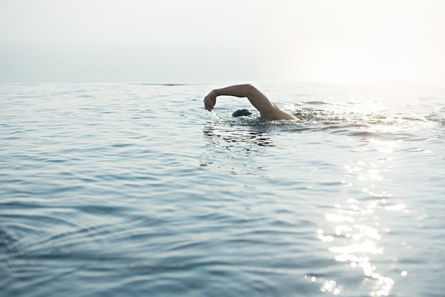 A man swimming for exercise in at swimming pool