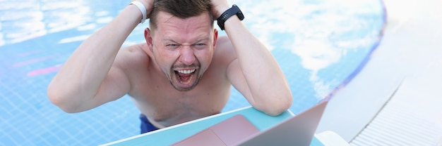 Man swimming in pool and tearing his hair in front of laptop screen