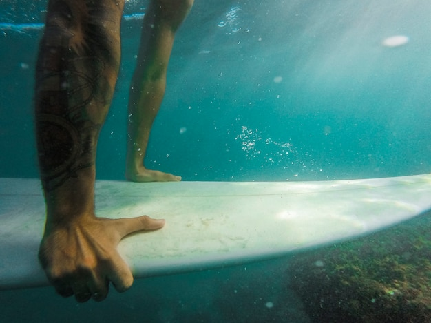 Man swimming on surfboard underwater