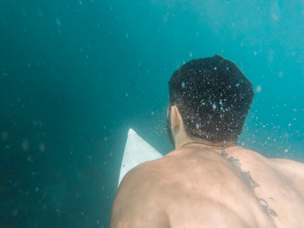 Man swimming on white surfboard underwater