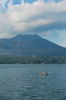 男は火山を見下ろすボートで泳ぎます。