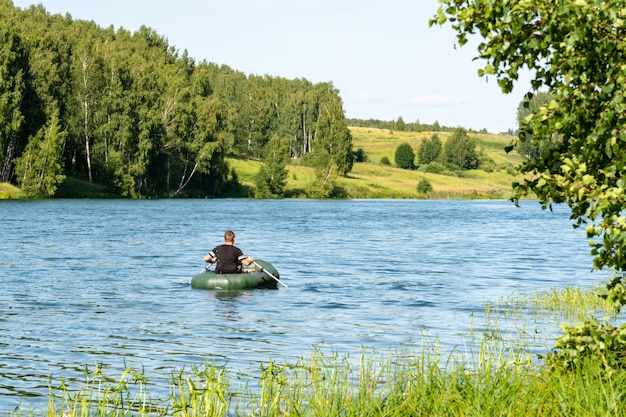 A man swims in an inflatable boat on the river against the background of forests and meadows.
