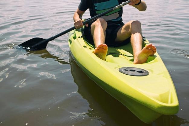 男は湖のカヤックで泳ぐ