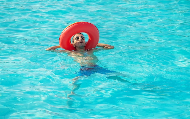 Man swims in a pool with a circle.
