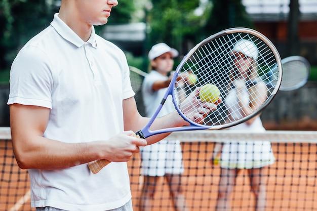テニスラケットを両手で振って強烈なシュートを放つ男。試合前の夜に練習します。