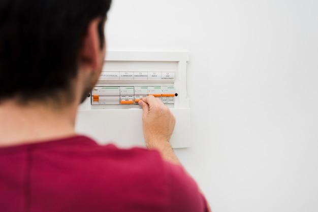 Человек, отключив электрический предохранитель в электрической коробке на стене