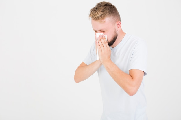 Man in t-shirt blowing nose
