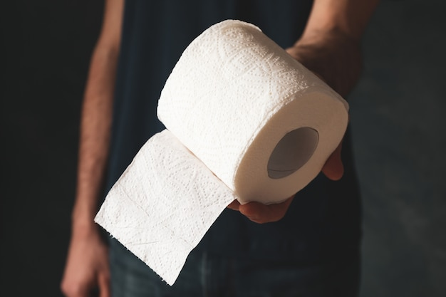 Man in t-shirt holds toilet paper